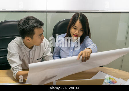 Asian business employees discuss about work on paper - Stock Photo