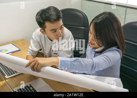Two Asian office employee discuss about information on paper - Stock Photo