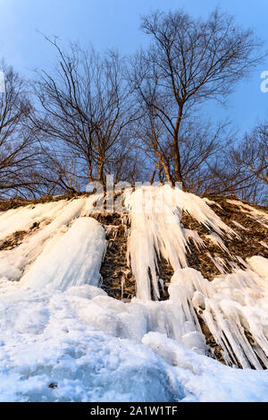 Sunrise at frozen river. Ice snow and big icicles on a bank cliff - Stock Photo