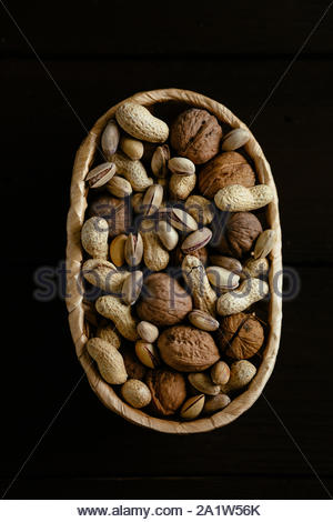 Nuts in basket. Mixed organic nuts in basket on black background. Group of different nuts - Stock Photo