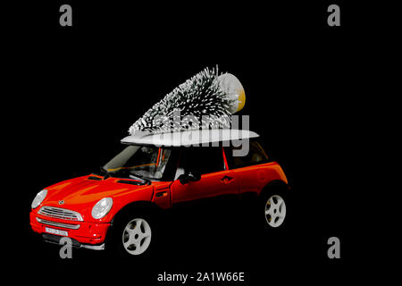 Red car with Christmas tree on the roof. - Stock Photo