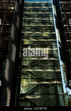 Reflections in the glass front of a modern high rise, glass and steel office building. - Stock Photo