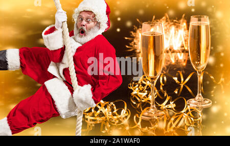 Happy Christmas Santa Claus climbing on rope with glasses of champagne in background. Caucasian male model in traditional costume. Concept of holidays, new year's, winter mood, gifts. Copyspace. - Stock Photo
