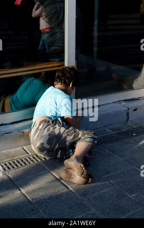 Istanbul, Turkey, March 07,2019: homeless young  barefoot boy lying next to the shop window on the street of Istanbul, face away from camera - Stock Photo