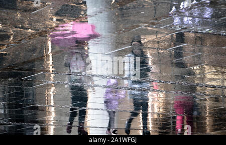 Blurry reflection shadow silhouette of people and a child walking together under umbrella, on a rainy day on a wet city street - Stock Photo