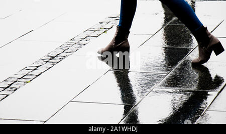 Silhouette shadow and reflection of a woman in  ankle boot shoes walking wet city street on a rainy day, legs only - Stock Photo