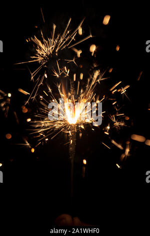 Sparkler- A person holding a burning sparkler isolated on black background. Holiday background image for diwali, christmas, new year, birthday celebra - Stock Photo
