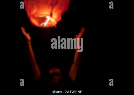 Blurred abstract background image of person flying or launching red sky lantern at night during diwali, new year, christmas concept with space for tex - Stock Photo