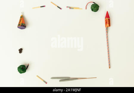 Flat lay of different types of Diwali Firecrackers arranged in frame for copy space on isolated background - Stock Photo