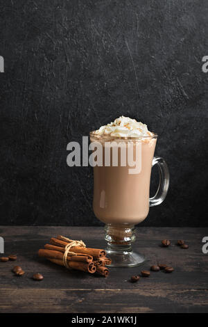 Irish Coffee with whipped cream on black wooden background, copy space.