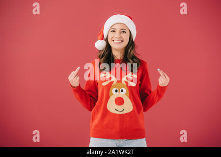 attractive and smiling woman in santa hat and sweater showing middle fingers isolated on red - Stock Photo