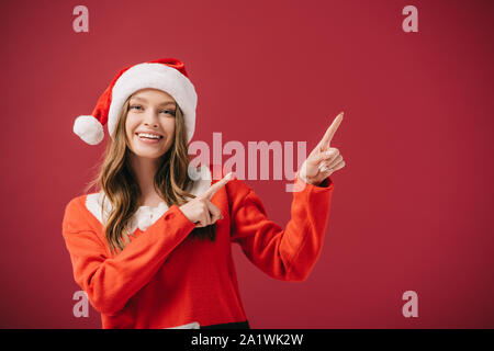 attractive woman in santa hat and sweater pointing with fingers isolated on red - Stock Photo