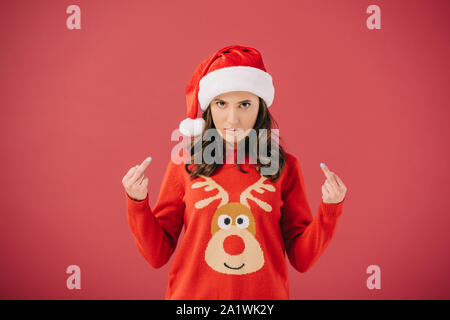 attractive and angry woman in santa hat and sweater showing middle fingers isolated on red - Stock Photo