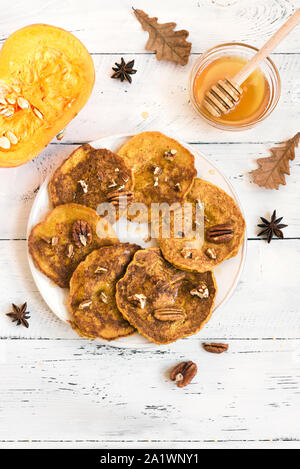 Pumpkin pancakes with pecan and honey on white table, top view, copy space. Traditional autumnal healthy breakfast - pumpkin pancakes. - Stock Photo