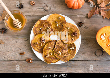Pumpkin pancakes with pecan and honey on wooden table, top view, copy space. Traditional autumnal healthy breakfast - pumpkin pancakes. - Stock Photo