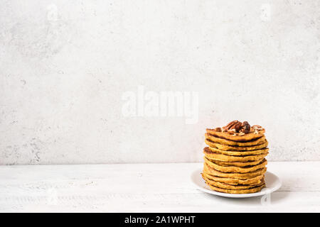 Pumpkin pancakes with pecan and honey on white table, copy space. Traditional autumnal healthy breakfast - stack of pumpkin pancakes. - Stock Photo