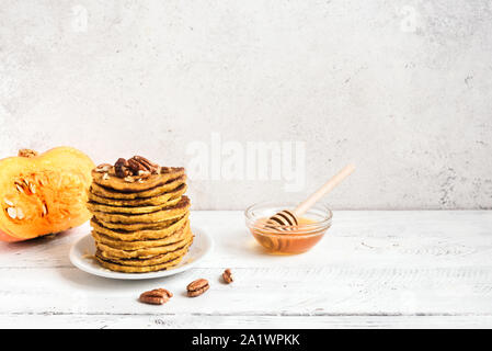 Pumpkin pancakes with pecan and honey and organic pumpkin on white table, copy space. Stack of pumpkin pancakes. - Stock Photo