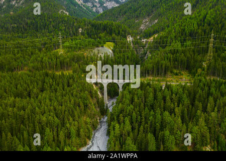 Inn River flowing in the forest in Switzerland. Aerial view from drone on an old railway bridge viaduct in the mountains - Stock Photo