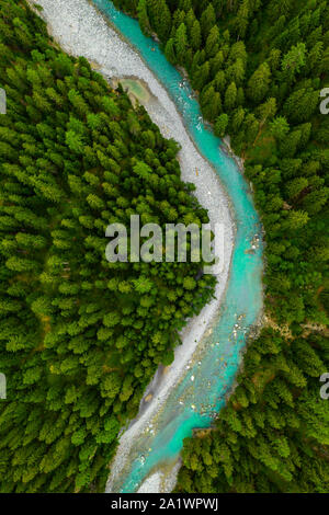 Inn River flowing in the forest in Switzerland. Aerial view from drone on a blue river in the mountains - Stock Photo
