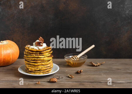 Pumpkin pancakes with whipped cream, pecan and honey on rustic background, copy space. Traditional autumnal healthy breakfast - stack of pumpkin panca - Stock Photo
