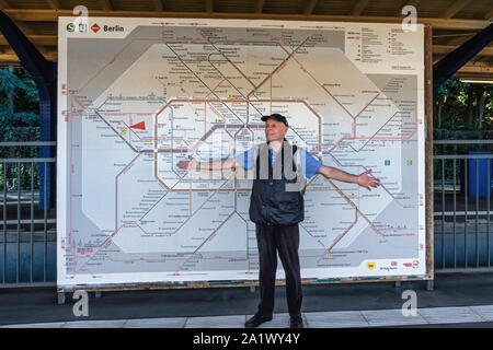 Elderly male tourist stands in front of Berlin BVG transport map. Map of S-bahn, U-Bahn and trams in Berlin, Germany - Stock Photo
