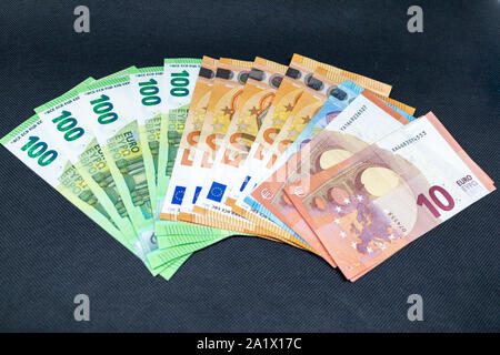 a lot of euro banknotes lying spread out on a dark table