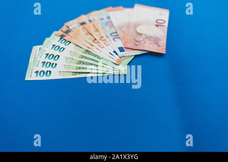 a lot of euro banknotes lie spread out on a blue base