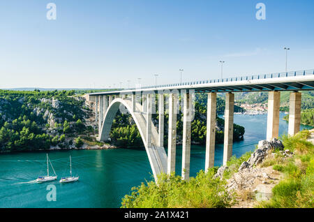 Small town of Skradin on Krka river, the entrance to the Krka National Park. Two yachts swimming into towns port under the big bridge. - Stock Photo