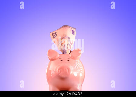 Piggy bank from the front on isolated blueish background - Stock Photo