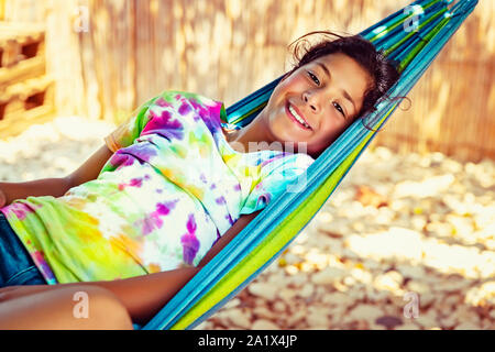 Little girl relaxing in hammock on the beach, with pleasure spending time near the sea, enjoying happy active summer vacation - Stock Photo