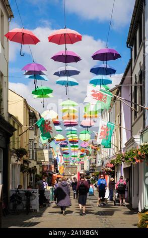 Art installation colourful display of umbrellas hanging above a busy narrow sunlit street in old town. Stryd y Plas, Caernarfon, Gwynedd, Wales, UK