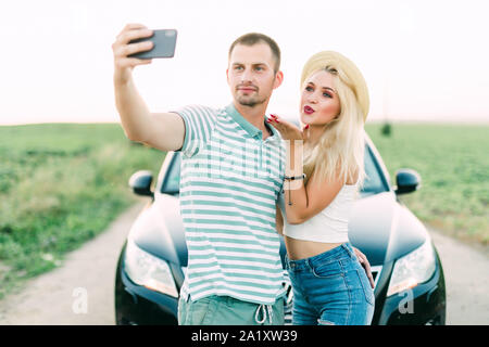 Young in loved couple take selfie in front of their car - Stock Photo