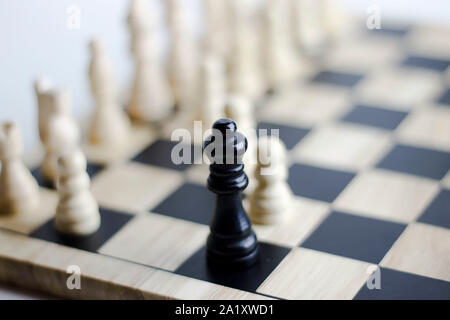 Checkmate and stalemate. Focus on a queen. Victory concept. Chess game on a chess board.