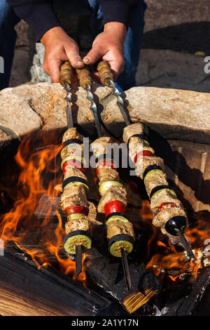 Men's hands hold three kebabs with vegetables over a fire. View from above - Stock Photo
