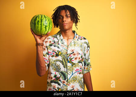Afro american man with dreadlocks holding watermelon over isolated yellow background with a confident expression on smart face thinking serious - Stock Photo