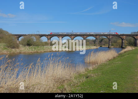 Passenger train crossing Dutton Viaduct, a 19th-century railway viaduct over the River Weaver in Cheshire, UK