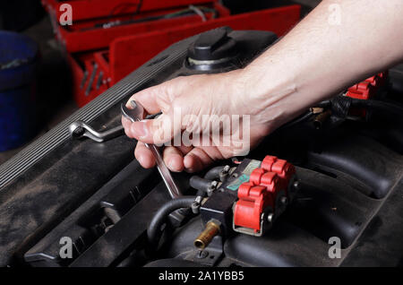 Car service - Engine repair, mechanic hand with wrench spins nut on intake manifold - Stock Photo