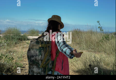 Girl traveler walks across the field and holds out his hand. Follow me - Stock Photo
