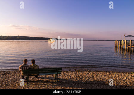 Couple on bench looking at the chiemsse bavaria - Stock Photo