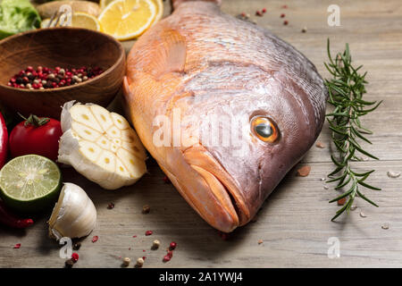 Fresh raw red snapper fish with spices, herbs and vegetables for cooking on wooden background. - Stock Photo