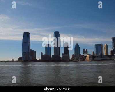 The Jersey City, NJ skyline along the Hudson River with Ellis Island . The waterfront is now called the Gold Coast because of redevelopment. - Stock Photo
