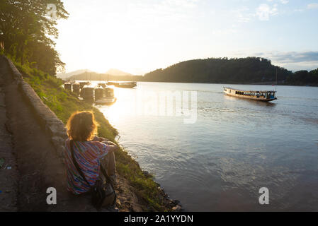 Woman looking at boats on Mekong River at Luang Prabang Laos, sunset dramatic sky, famous travel destination backpacker in South East Asia
