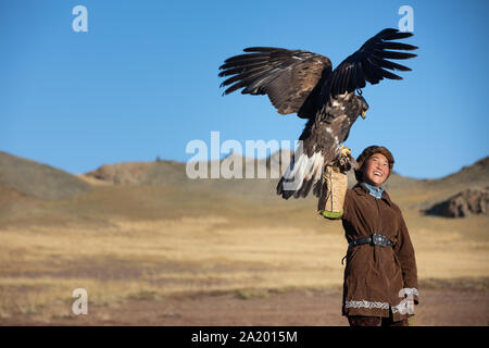 Traditional kazakh eagle hunter girl with his golden eagle that is used to hunt for fox and rabbit fur. Ulgii, Western Mongolia. - Stock Photo