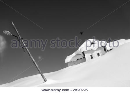 Kashmir, India. A faint moon emerges and a crow flies over an army camp in Gulmarg. On days when the violence does not erupt, a delicate calm is maintained.  March 12, 2014. - Stock Photo