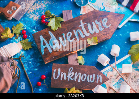 Road sign with Adventure and Unknown directions. Travel essentials creative header with socks, maps, and marshmallows, wanderlust concept - Stock Photo