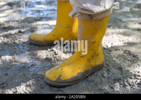 Construction worker in yellow rubber boots at the construction site, compacting the concrete - Stock Photo