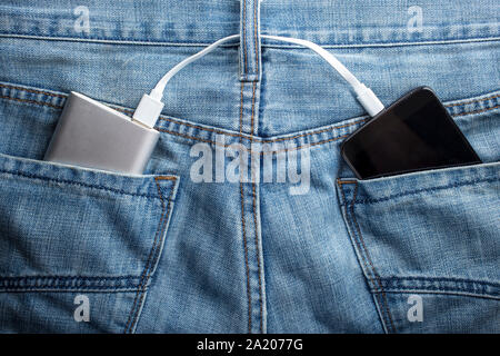 power bank lies in a back pocket of jeans, in the other is a mobile phone that is charged - Stock Photo