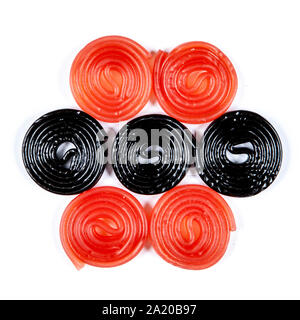 red and black licorice wheels on a white background - Stock Photo