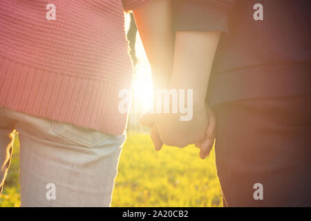 Two child girls holding hands during amazing sunset - Stock Photo