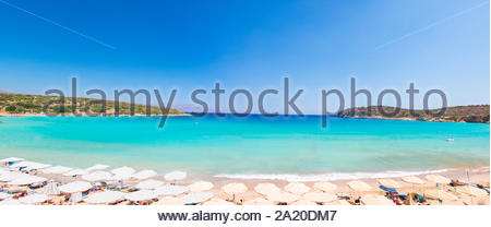 Beautiful colorful beach at Crete island, Greece. Voulisma paradise beach with umbrella and sunbeds.  Summer vacation travel holiday background concep - Stock Photo